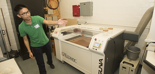 Student showing off the brand new CNC laser in the Machine Room.