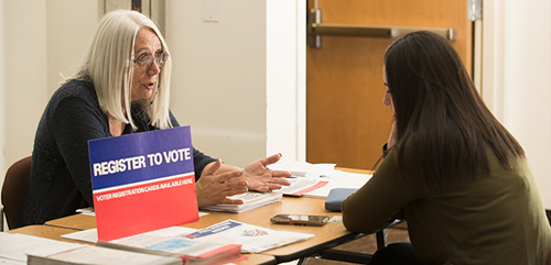 Cindy Reul of the League of Women Voters talks a student through the process of registering to vote during the Election Fair